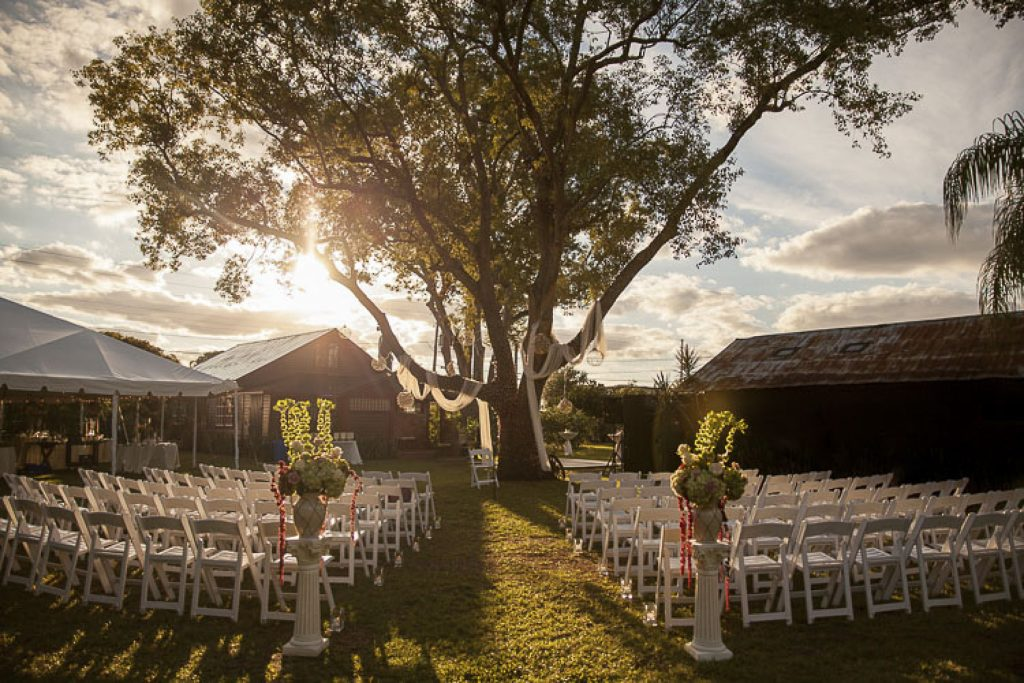 outdoor wedding venue with chairs in front of a tree at sunset