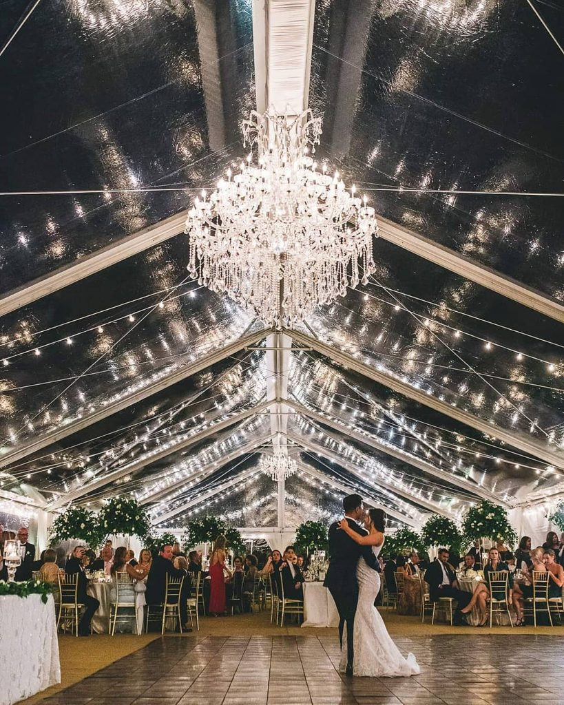 bride and groom during their first dance under a chandelier
