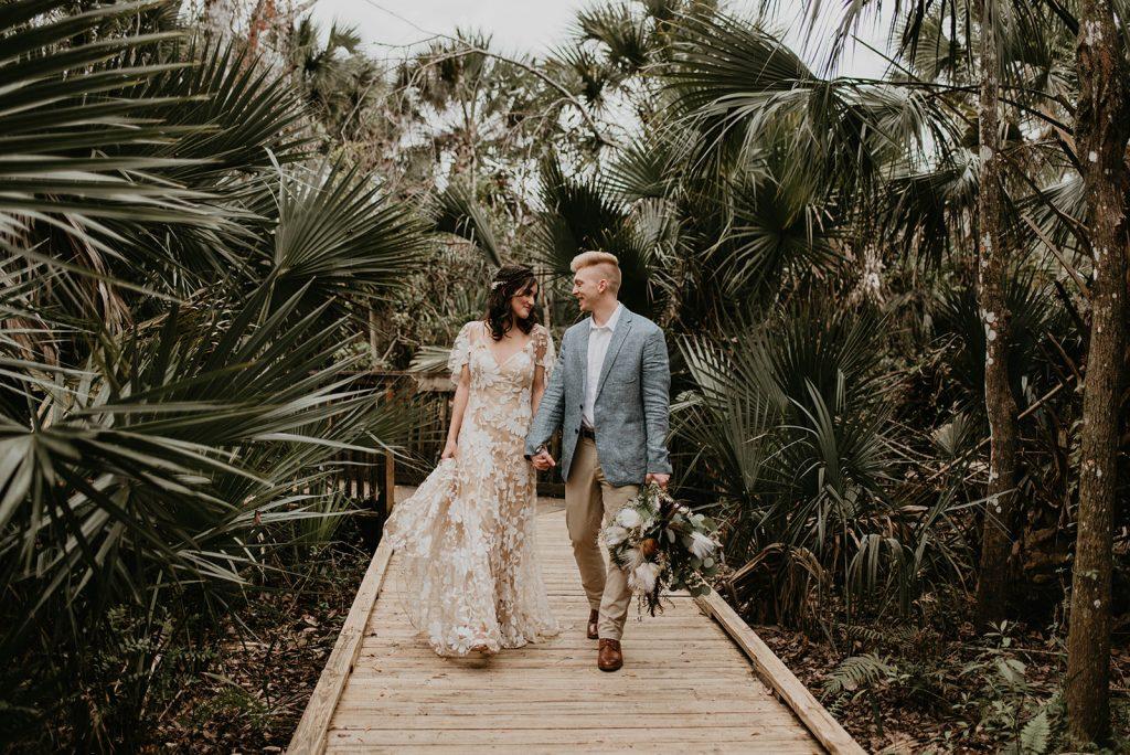 bride and groom walking through trees
