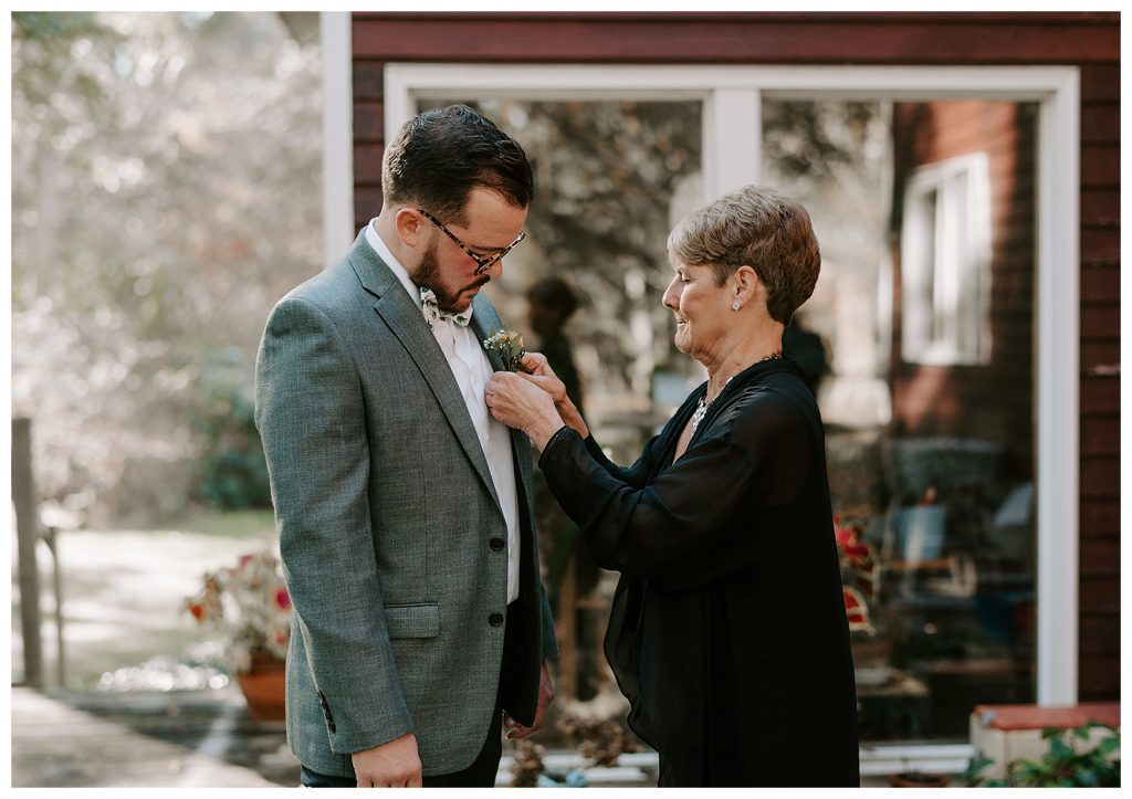groom's mom putting boutonniere on