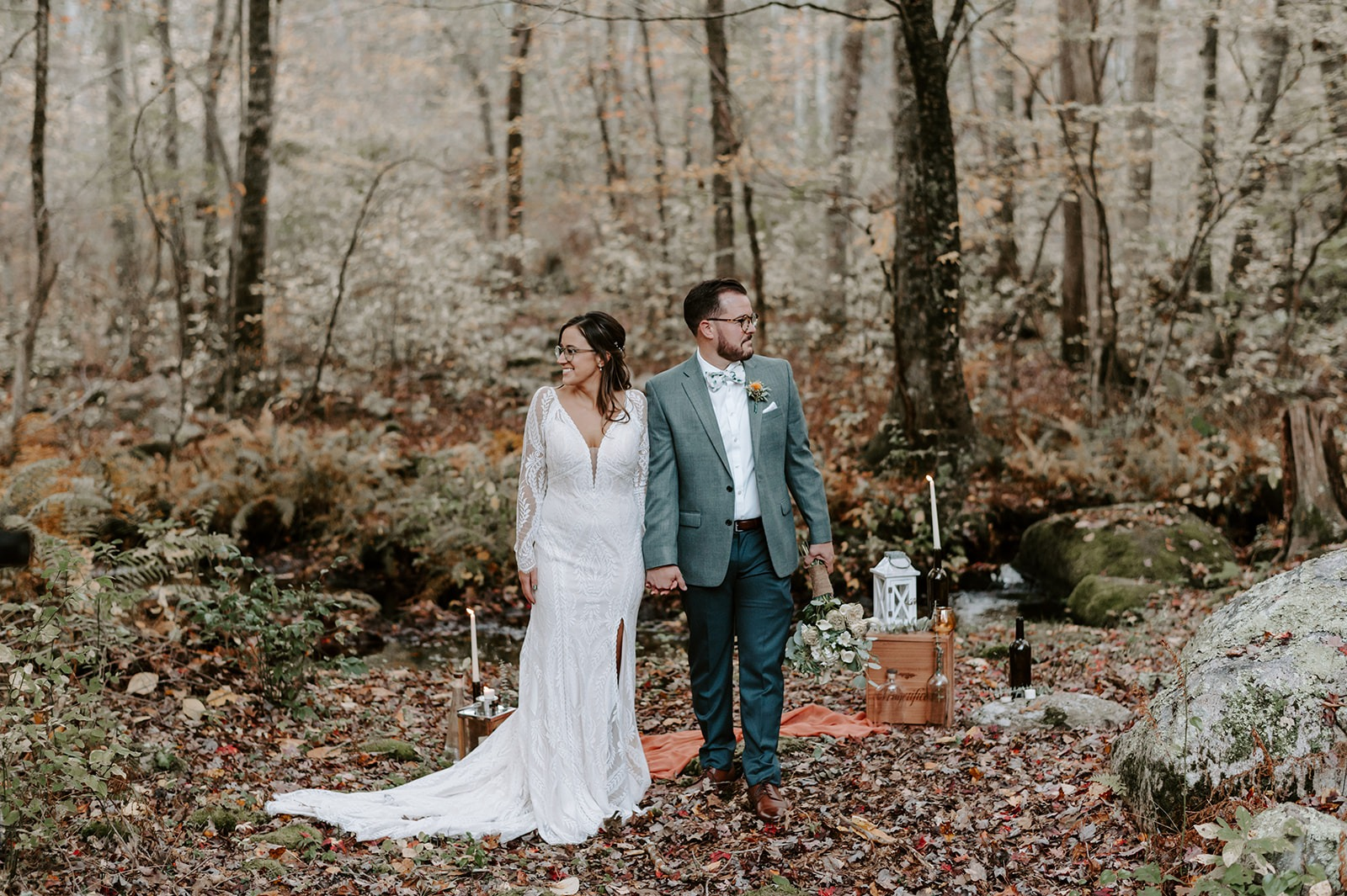 bride and groom standing in woods
