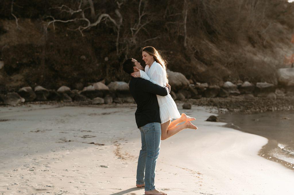 man holding woman on a beach