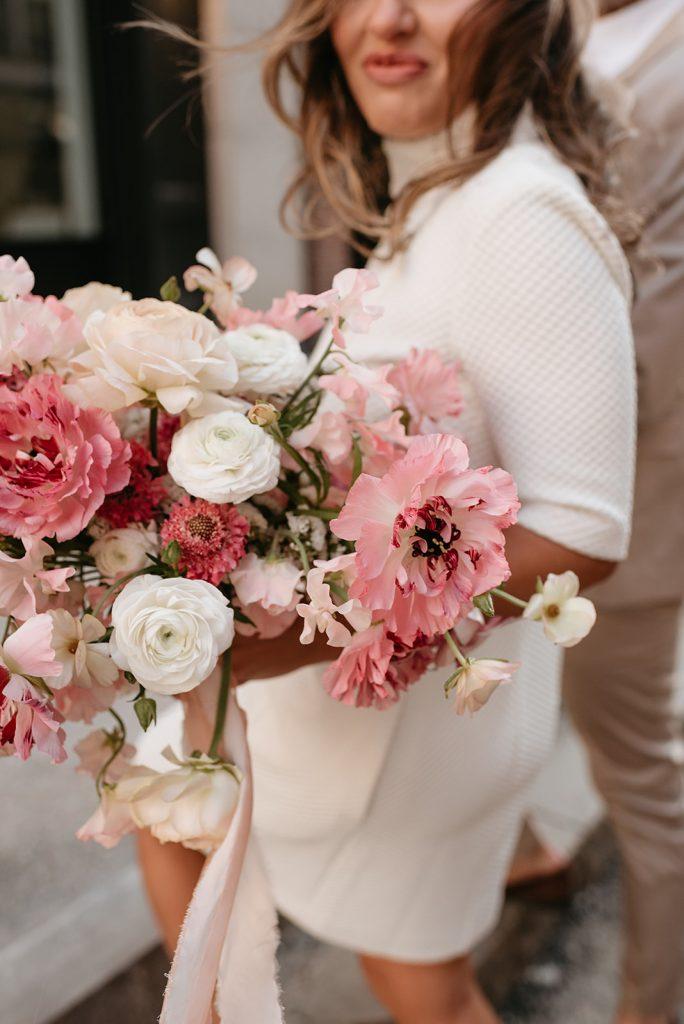 bride holding pink floral bouquet