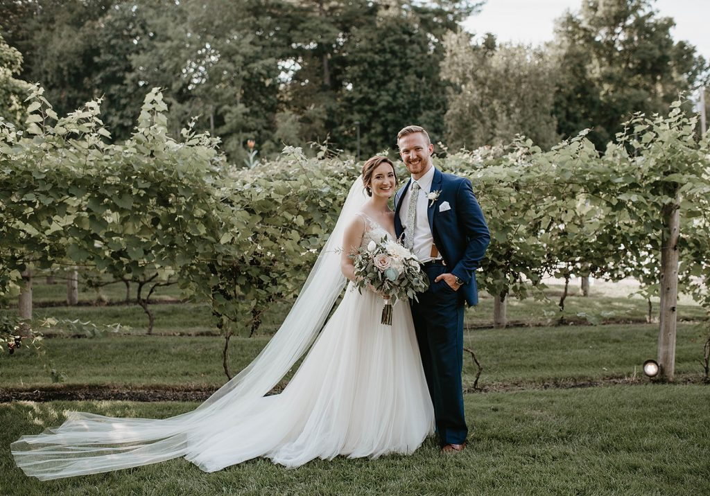 a bride and groom portrait in a field