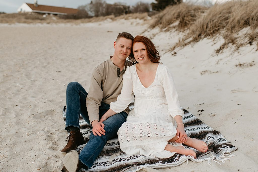 couple smiling at camera on a beach